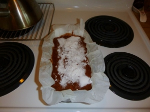Pound cake batter topped with white sugar and grated coconut before it has been placed in the oven.