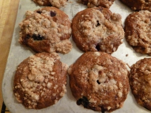 A close up of the topping on four berry muffins still in the pan.